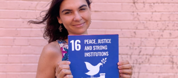 "Woman holding sign that says ""16 Peace, Justice and Strong Institutions"""